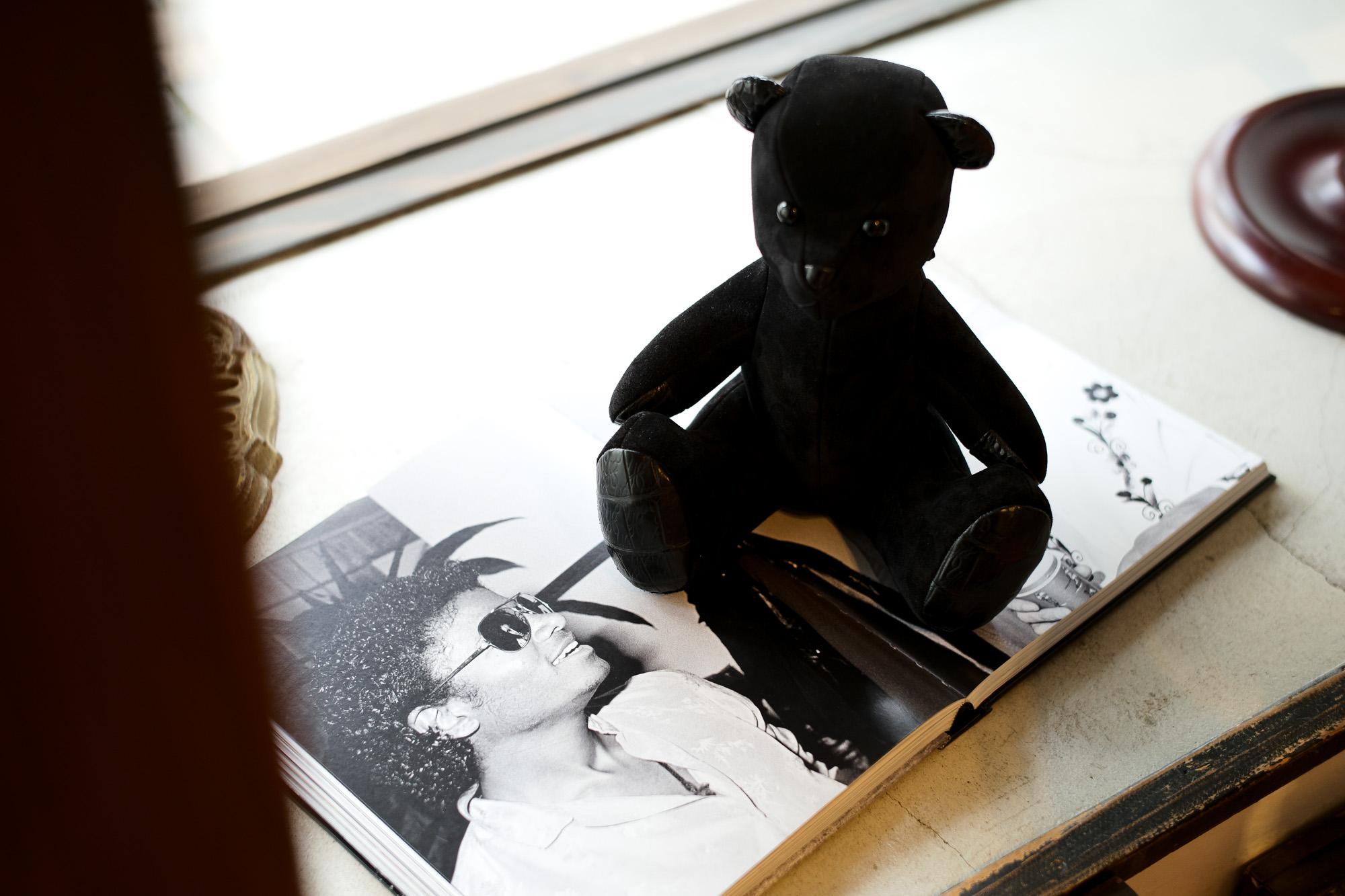 Yohei Fukuda The Teddy Bear ヨウヘイフクダ テディベア Alto e Diritto altoediritto アルトエデリット 愛知 名古屋 お客さまから何世代も受け継ぐ事の出来るテディベアが欲しいといったご要望から、パターンから手作りでテディベアを製作しました。もし靴職人が本気でテディベアを作ったら?といったコンセプトを元に靴のディテールを取り入れました。1点1点手作りの為、革や表情がすべて異なります。靴にも使用する厳選した革を使い、手、足、鼻、耳には贅沢なクロコダイルを使用した世界で1つだけのテディベアとなります。ネームプレートにはシリアルナンバー、生年月日が記載されます。お客さまで名前をご記入頂き、お愉しみください。サイズ:H253mm x W230mm x D185mm 素材:本体は牛革スエード   素材:足、手、鼻、耳はクロコダイル(足の裏にロゴが入っております。) 特注品のガラスを目に使用しています。 口は靴にも使われるシャコ止めで縫われています。 背中は靴のようにハトメを採用しています。 付属品:オリジナルポーチ、桐箱付き 日本製