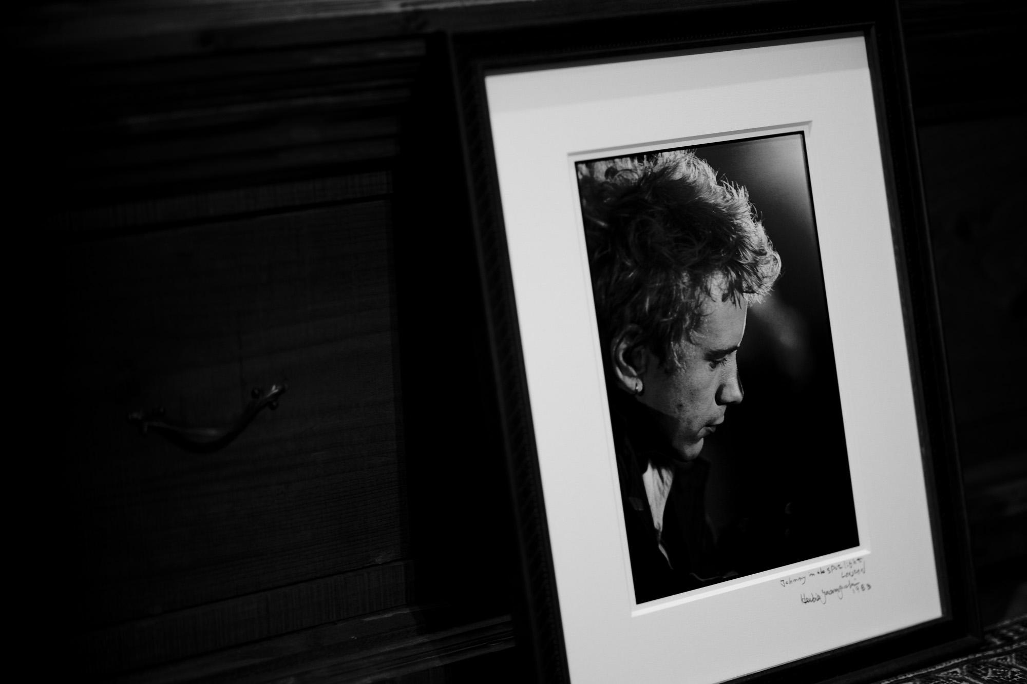 """Johnny in the spot light LONDON / HERBIE YAMAGUCHI 1983 ジョニーロットン スポットライト ロンドン 1983年 撮影 ハービー山口 写真家 Johnny Rotten ジョニー・ロットン John Lydon ジョン・ライドン パンク・ロックバンド、セックス・ピストルズのリード・ボーカルを務め、解散後はパブリック・イメージ・リミテッド(PiL)を結成した。 ジョニー・ロットンという名前は彼がセックス・ピストルズに加入したとき、ギタリストのスティーヴ・ジョーンズが彼の歯の汚い状態を見て「腐ってる!お前の歯、腐ってるぞ!(You're rotten! Look at you, your teeth are rotten!)」と発言したことがきっかけで彼のニックネームとなった[1]。 セックス・ピストルズセックス・ピストルズ時代 (1977年) 小学生時代とは打って変わり、中学生からのライドンは退学処分を受けるほどの不良となり、10代後半はマルコム・マクラーレン(デザイナーのヴィヴィアン・ウエストウッドが共同経営者)のブティック「Sex」に頻繁に出入りするようになる[3]。この店を溜まり場としていたライドンをリーダー格とする不良グループ""""ジョンズ""""は、メンバー全員の名がjohnであることから名づけられた。1975年にマクラーレンがアメリカのバンド、ニューヨーク・ドールズとの小ツアーから帰り、スティーヴ・ジョーンズやポール・クックと共に新たなバンドの結成を模索していたとき、ライドンが現れた。ライドンは「I Hate」とサインペンでなぐり書きされたピンク・フロイドのTシャツを着ており、店内でのオーディションでアリス・クーパーの「エイティーン」を歌った[3]。そしてバンドへ加入、バンド名はセックス・ピストルズに決まる。ピストルズは「アナーキー・イン・ザ・UK」や「ゴッド・セイヴ・ザ・クイーン」などの歴史的な曲を発表し、パンクの有名バンドとなった。曲は主に、メンバーのグレン・マトロックが書いていた。ピストルズの後期、ライドンは、ヘロイン中毒である親友のシド・ヴィシャスの薬物治療の手助けをするが、結局シド・ヴィシャスはヘロインをやめられずまともに演奏できる状態ではなくなった。メンバー間の不仲も頂点に達し、バンドは最悪の状態になり、1978年1月14日、アメリカツアーのサンフランシスコ最終公演を最後にライドンは脱退を表明。ラストライブの最後に「騙された気分はどうだい」と言い放っている[7][8]。脱退表明時には「ロックは死んだ」と宣言した[9]。後に、シド・ヴィシャスと恋人のナンシーは死亡している。Brian Setzer Stray Cats LONDON / HERBIE YAMAGUCHI 1981 ブライアン セッツァー ストレイキャッツ ロンドン 1981年 愛知 名古屋 Alto e Diritto altoediritto アルトエデリット ハービー山口 HERBIE YAMAGUCHI 写真家 Thames LONDON / HERBIE YAMAGUCHI 1983 テムズ川 ロンドン ハービー山口 1983年 イギリス England イングランド 写真家 写真 http://www.herbie-yamaguchi.com/ オリジナルプリント Portrait Joe 地下鉄のジョー パンク Punk 愛知 名古屋 Alto e Diritto altoediritto アルトエデリット 革ジャン レザージャケット ライダースジャケット モヒカン 鋲ジャン 1983年イギリス総選挙 イギリス名誉革命史 United Kingdom General Election, 1983 ハービー・山口は写真家、エッセイスト。 東京都大田区出身。 作家名の由来は、自身が傾倒していたジャズ・フルート奏者のハービー・マンから。山口 芳則 「LONDON AFTER THE DREAM」(流行通信社 1985)「LEICA LIVE LIFE」福山雅治写真集 (ソニーマガジンズ 1994)「代官山17番地」(アップリンク 1998)「尾崎豊」(光栄 1998)「DISTANCE」福山雅治写真集 (アミューズブックス 1999「TIMELESS IN LUXEMBOURG」 (ルクセンブルク大公国大使館 1999)「bridge22 LP」山崎まさよし×ハービー・山口(ソニーマガジンズ 2001)「LONDON CHASING THE DREAM 」(カラーフィールド 2003)「peace」(アップリンク 2003)フジテレビドラマ「優しい時間―富良野にて」(フジテレビ出版 2005"""